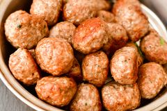 Meat balls. Vintage cast-iron pan with tomatoes, onions and peppers, herbs on wooden rustic background top view close up, black pepper , red chili peppers royalty free stock photo