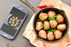 Meat balls  with parsley in vintage cast-iron pan. Meat balls in a cast iron pan and a smartphone with the photo next to it with tomatoes, onions and peppers Royalty Free Stock Images