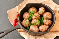 Meat balls  with parsley in vintage cast-iron pan. Meat balls vintage cast-iron pan with tomatoes, onions and peppers, herbs on wooden rustic background top view Royalty Free Stock Photos