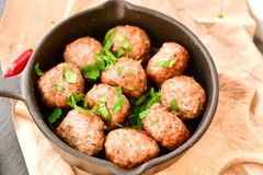 Meat balls  with parsley in vintage cast-iron pan. Meat balls vintage cast-iron pan with tomatoes, onions and peppers, herbs on wooden rustic background top view Royalty Free Stock Image