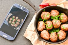 Meat balls  with parsley in vintage cast-iron pan. Meat balls in a cast iron pan and a smartphone with the photo next to it with tomatoes, onions and peppers Royalty Free Stock Photography