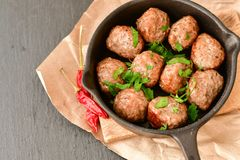 Meat balls  with parsley in vintage cast-iron pan. Meat balls in a cast iron pan and a smartphone with the photo next to it with tomatoes, onions and peppers Stock Photography