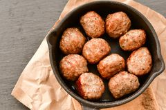 Meat balls  with parsley in vintage cast-iron pan. Meat balls in a cast iron pan and a smartphone with the photo next to it with tomatoes, onions and peppers Stock Photos
