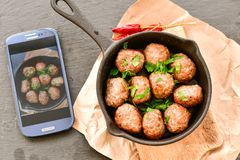 Meat balls  with parsley in vintage cast-iron pan. Meat balls in a cast iron pan and a smartphone with the photo next to it with tomatoes, onions and peppers Stock Images