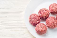 Meat balls from raw beef force-meat on a white plate. Fresh raw meat balls white plate on wooden background, close-up Royalty Free Stock Photography