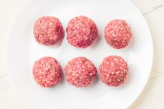 Meat balls from raw beef force-meat on a white plate. Fresh raw meat balls white plate on wooden background, close-up Stock Photography