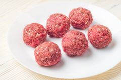 Meat balls from raw beef force-meat on a white plate. Fresh raw meat balls white plate on wooden background, close-up Royalty Free Stock Photo