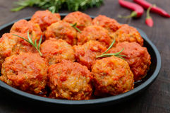 Meat balls in spicy tomato sauce served on a cast iron pan on a dark wooden background. Stock Photography
