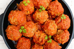 Meat balls in spicy tomato sauce served on a cast iron pan on a white wooden background. Royalty Free Stock Images