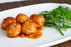 Meat balls in tomato sauce. On a white dish with some parsley leaves stock images