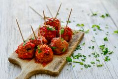 Meat balls with tomato sauce and fresh parsley on cutting board royalty free stock image