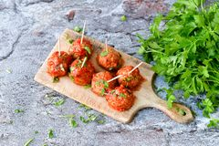 Meat balls with tomato sauce and fresh parsley on cutting board stock photo