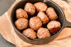 Meat balls  in vintage cast-iron pan. Meat balls in a cast iron pan and a smartphone with the photo next to it with tomatoes, onions and peppers, herbs on wooden Stock Images