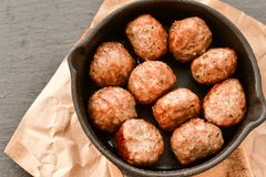 Meat balls  in vintage cast-iron pan. Meat balls in a cast iron pan with tomatoes, onions and peppers, herbs on wooden rustic background top view close up, black Royalty Free Stock Photos