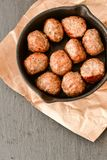 Meat balls  in vintage cast-iron pan. Meat balls in a cast iron pan with tomatoes, onions and peppers, herbs on wooden rustic background top view close up, black Royalty Free Stock Images