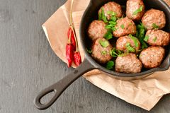 Meat balls  in vintage cast-iron pan. Meat balls in a cast iron pan with tomatoes, onions and peppers, herbs on wooden rustic background top view close up, black Stock Image