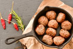 Meat balls  in vintage cast-iron pan. Meat balls in a cast iron pan with tomatoes, onions and peppers, herbs on wooden rustic background top view close up, black Stock Photography