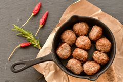 Meat balls  in vintage cast-iron pan. Meat balls in a cast iron pan with tomatoes, onions and peppers, herbs on wooden rustic background top view close up, black Royalty Free Stock Photo