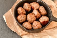 Meat balls vintage cast-iron pan. With tomatoes, onions and peppers, herbs on wooden rustic background top view close up, black pepper , red chili peppers Royalty Free Stock Photos