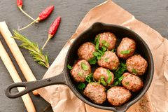 Meat balls  with parsley in vintage cast-iron pan. Meat balls vintage cast-iron pan with tomatoes, onions and peppers, herbs on wooden rustic background top view Royalty Free Stock Photo