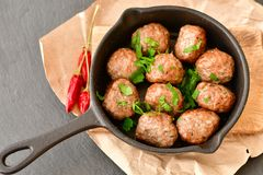 Meat balls  with parsley in vintage cast-iron pan. Meat balls vintage cast-iron pan with tomatoes, onions and peppers, herbs on wooden rustic background top view Royalty Free Stock Photography