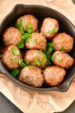 Meat balls  with parsley in vintage cast-iron pan. Meat balls vintage cast-iron pan with tomatoes, onions and peppers, herbs on wooden rustic background top view Stock Image