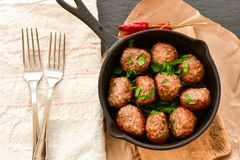 Meat balls  with parsley in vintage cast-iron pan. Meat balls vintage cast-iron pan with tomatoes, onions and peppers, herbs on wooden rustic background top view Stock Photography