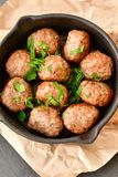 Meat balls  with parsley in vintage cast-iron pan. Meat balls vintage cast-iron pan with tomatoes, onions and peppers, herbs on wooden rustic background top view Stock Photos