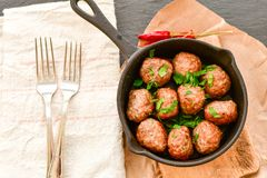 Meat balls  with parsley in vintage cast-iron pan. Meat balls vintage cast-iron pan with tomatoes, onions and peppers, herbs on wooden rustic background top view Stock Photo
