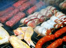 Meat on barbecue. Various meat grilled on barbecue in smoke Royalty Free Stock Image
