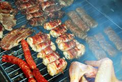 Meat on barbecue. Various meat grilled on barbecue in smoke Stock Photos