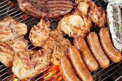 Meat on the barbecue grill. Various meats like chicken, sausage, steak and corn wrapped in aluminum foil on a barbecue grill Stock Image
