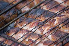 Meat barbecue. Sausages with cheese spun in bacon on a metal grill close-up royalty free stock photo