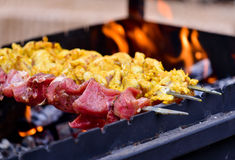 Meat barbeque skewers on fire Stock Photos