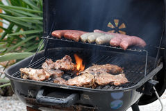 Meat on BBQ. Meat and sausages on the BBQ stock image