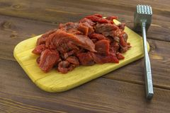 Meat beef cut into pieces lies on a wooden Board. Metal Hammer for beating meat stock image