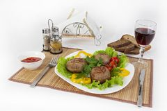 Meat of beef, round rhizol. Round meat cutlets with greens, tomatoes and a glass of wine. Useful and tasty breakfast. stock photography