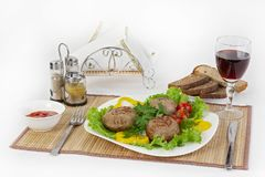 Meat of beef, round rhizol. Round meat cutlets with greens, tomatoes and a glass of wine. Useful and tasty breakfast. stock image