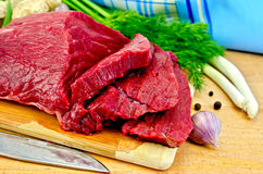 Meat beef on a wooden board with a knife. A piece of beef, garlic, pepper pots, dill, green onions, ginger root, blue napkin, a knife on a wooden board Stock Image