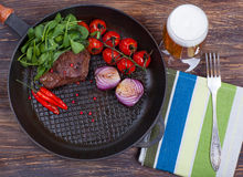 Meat, beer and vegetables in frying pan Royalty Free Stock Photography