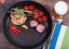 Meat, beer and vegetables in frying pan Stock Photos