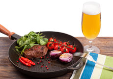 Meat, beer and vegetables in frying pan isolation Stock Photo