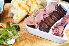 Meat Board. Selection of fine cured meats including Kobashz, Lamb, Pastrami on a chopping baord with salad Stock Photos