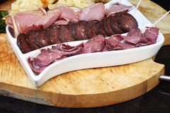 Meat Board. Selection of fine cured meats including Kobashz, Lamb, Pastrami on a chopping baord with salad Stock Images