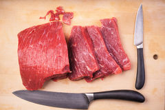 Meat on the board. Sliced meat on the board with knives Stock Photos