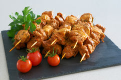 Meat brochettes on a black slate tray. With some tomatoes and parsley Stock Photos