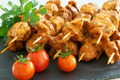 Meat brochettes on a black slate tray. With some tomatoes and parsley Stock Photo