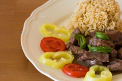 Meat with brown rice and garnish. On white plate Royalty Free Stock Photos