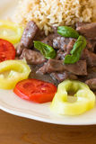 Meat with brown rice and garnish Stock Photos
