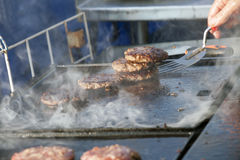 Meat burgers being cooked on an outdoor gas cooker Stock Images